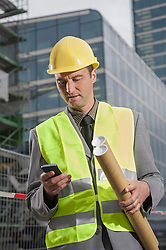 Site manager holding blueprints and text messaging on a mobile phone