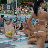 Viewers watch participant Petra Viktoria Ihasz attend the Miss Bikini Hungary beauty contest held in Budapest, Hungary on August 06, 2011. ATTILA VOLGYI