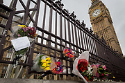 A floral memorial on the railings of the Houses of Parliament while Londoners gather on Westminster Bridge, the scene of the Terrorist attack 7 days ago in which 4 people died and others severely injured, on 29th March 2017, London, England. Hundreds crossed the Thames in a silent vigil to commemorate the four and at 2.40pm when Khalid Masood drove into crowds on the bridge before stabbing a police officer at the nearby Palace of Westminster, the crowds fell silent, many bowing their<br /> heads.