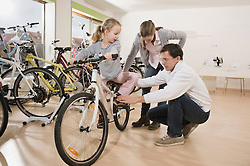 Salesman instructing girl about bicycle riding