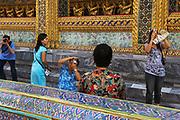 Tourists taking photos, Wat Phra Kaew - Temple of the Emerald Buddha - in the Dusit area of Bangkok.