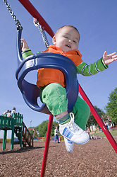 Baby boy swinging in an infant's swing at the playground,