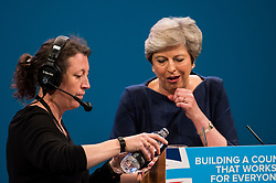 © Licensed to London News Pictures. 04/10/2017. Manchester, UK. British prime minister THERESA MAY is given a drink of water while delivering her leaders speech on the final day of the Conservative Party Conference. The four day event is expected to focus heavily on Brexit, with the British prime minister hoping to dampen rumours of a leadership challenge. Photo credit: Ben Cawthra/LNP