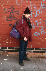 Young boy standing in street holding kit bag after running away from home,