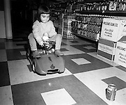 Electric Car Race at Supermarkets.<br /> 1971.<br /> 30.10.1971.<br /> 10.30.1971.<br /> 30th October 1971.<br /> Elect car races were held in Powers Supermarkets in Stillorgan,Blackrock Co Dublin and in Bray Co Wicklow.<br /> <br /> Five year old Adrienne Mooney is the picture of concentration as she avoids obstacles placed on the shop floor.
