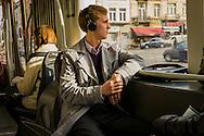 Man in tram 7 met koptelefoon en lange grijze regenjas kijkt naar buiten