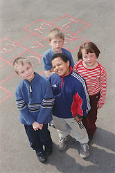 Multiracial group of children standing together in school playground,