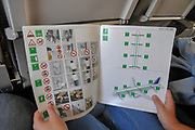 interior of the cabin of a Lufthansa Airbus A321 passenger is reading the safety manual