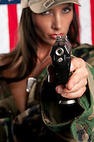 Young woman wearing military uniform pointing with gun. Use of selective focus. Focus in gun.