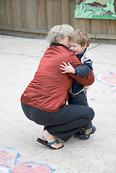 Grandmother hugging young boy at nursery,