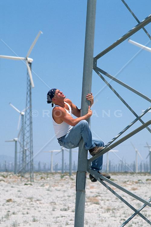 Man climbing a windmill in Palm Springs, Ca