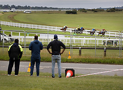 © Licensed to London News Pictures. 04/07/2020. Epsom, UK. A small crowd watch from outside a security fence as the first outing of the Derby Day race meeting takes place as the riders in The Investec Woodcote EBF Stakes pas by. Today's race meeting is being held behind closed doors due to the coronavirus lockdown rules. Seven races are being held in one day including The Oaks, with The Derby being run at 4:55pm. Photo credit: Peter Macdiarmid/LNP