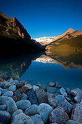 Victoria Peak is reflected in the relatively calm waters of Lake Louise at sunrise in Banff National Park, Alberta, Canada.