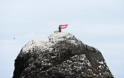 Nick Hancock unfurls his Scottish Sun flag on the top of Rockall, for his reconnaissance mission for a future 60 day occupation of Rockall. The Rockall Jubilee Expedition, a unique endurance expedition to be undertaken by Nick, in order to raise funds for Help for Heroes .©Michael Schofield..