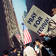 During a journey into America's hinterlands, days after the September 11th attacks in New York and Washington DC, crowds of New Yorkers gathered at barriers where streets were closed, near Ground Zero, to offer help for volunteers: Spare beds offered, free food distributed, and  offers of salvation. A man here has a board urging prayer and revival for those feeling spiritually adrift. American flags hang from buildings and businessmen and tourists talk in the street with some wearing dust masks. In outpourings of grief, anger and patriotic rhetoric, flags were flown as never before as America sought to express their emotions and a unity. .