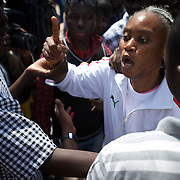 February 26, 2012 - Dakar, Senegal: Security men try to control a senegalese woman who was shouting insults against the president and candidate, Abdoulaye Wade, while voting at the Franco-Arab School in Point E area of Dakar. Hundreds of people queueing for voting insulted and heckled Wade, accusing the head of state of disrespect for the country's constitution when running for a third mandate. (Paulo Nunes dos Santos/Polaris)
