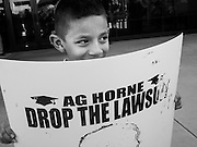17 OCTOBER 2013 - PHOENIX, AZ: ANDRES GARCIA, 6, gathers in front of the office of the Arizona Attorney General. About 100 people came to the office of Arizona Attorney General Tom Horne to protest the decision by Horne to sue community colleges in Maricopa County that charge DREAM Act students who are residents of Arizona out of state tuition rather than in state resident tuition. Nearly 10 people were arrested in a planned civil disobedience during the protest.      PHOTO BY JACK KURTZ