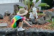 8 year old child wearing Akubra hat, inspecting small statues of a dog and two puppies. Kailua-Kona, Big Island, Hawaii