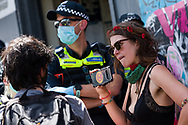A protester films during an Extinction Rebellion protest in Melbourne.  A small group of climate protesters marched from Flagstaff Gardens to The Queen Victoria Market and ending with two individuals gluing themselves together, and then glued themselves to Victoria Avenue outside of the Market. This comes as 5 new COVID-19 cases were uncovered in Melbourne's revamped Hotel Quarantine, breaking almost 40 days of virus free days. (Photo by Dave Hewison/Speed Media)
