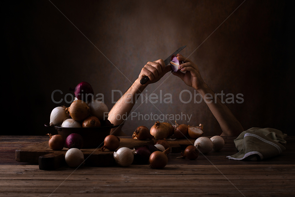 Hands of a man emerging from under a table peeling onions. Concept of someone hiding under the table so as not to cry when is peeling onions.<br /> Limited edition of 25 available as NFT on OpenSea: https://bit.ly/themysterybehindonions