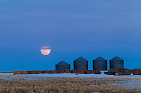 I took a trip out on the Prairie to the South and East of Calgary to watch the full moon rise at sunset. It was a spectacular sunset and the western sky was on fire as the sun dropped below the horizon.<br /> <br /> ©2013, Sean Phillips<br /> http://www.RiverwoodPhotography.com