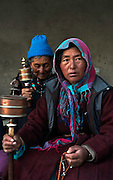 Pilgrims in prayer with their prayer wheels at Lamayuru Monastery.