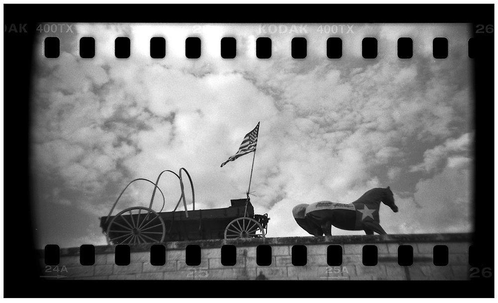 A wooden horse pulling a wagon is seen on the rooftop of a souvenir shop in Crawford, Texas, November 10, 2008. U.S. President George W. Bush moved to the small Texas town, population 705, in 1999 during his run for the presidency in 2000. The effect of the image was achieved by shooting 35mm black and white film in a medium format camera thereby exposing the entire negative including the sprocket holes of the film. REUTERS/Jim Young