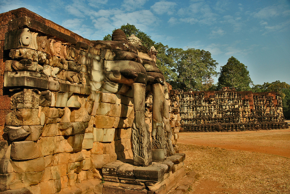 This image of the Terrace of the Leper King, a double terrace wall at the north end of the  Terrace of Elephants with deeply carved nagas, demons and other mythological beings was shot from in front of the Terrace of Elephants in Angkor Thom city, part of the Angkor complex in Siem Reap, Cambodia that includes the world's largest single religious monument, the breathtaking Angkor Wat. <br /> <br /> Angkor Thom city, at the center of which lies the amazing Bayon temple is the last and most enduring city of the Khmer empire. It was built by King Jayavarman VII as a fortified city of almost 4 sq miles or 10 sq km on the right bank of the Siem Reap River, a tributary of Tonle Sap Lake.<br /> <br /> It has been featured in many book, films and video games of pop culture most notably in the Angelina Jolie film, Lara Croft: Tomb Raider.