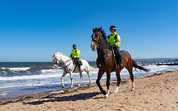 Portobello, Scotland, UK. 19 April 2020. Police horses patrol the promenade and beach at Portobello on sunny Sunday afternoon. Iain Masterton/Alamy Live News