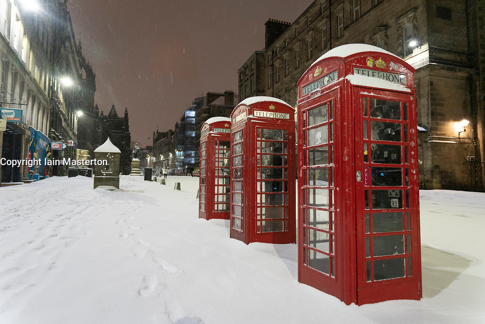 Edinburgh, Scotland, UK. 10 Feb 2021. Big freeze continues in the UK with heavy overnight and morning snow in the city. Pic; Three telephone boxes on an  empty Royal Mile in early morning snow.  Iain Masterton/Alamy Live news