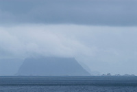 rugged mountain peaks of Væerøy rise from Vestfjord into arctic storm clouds, as seen from village of Å, Lofoten islands, Norway