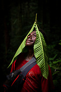 Kukusa, from the village of Likan in Papua New Guinea's East Sepik Province, poses with large leaves while walking in the rainforest near his village. (June 21, 2019)