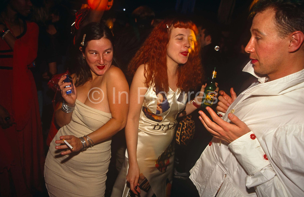 Two party girls are dancing with a male friend who is apparently flirting with the girl holding a packet of cigarettes and an unlit cigarette on the far left. Their body language suggests they know each other. The lady in the middle has red hair and lips and has her eyes closed and is holding a bottle of Hooch, an alcoholic drink. The party venue is dark and chaotic and the atmosphere is energetic and lively at a club venue called Adrenaline Village in Battersea, South London.