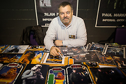 """© Licensed to London News Pictures . 06/12/2015 . Manchester , UK . Signing autographs , ALAN FLYNG who , as well as acting as an Imperial Officer , has appeared in countless films , is a costume supervisor and says he was lead chorister at Winston Churchill's funeral at St Paul's Cathedral . Fans attend Star Wars exhibition """" For the Love of the Force """" at Bowlers Exhibition Centre in Manchester . Photo credit : Joel Goodman/LNP"""