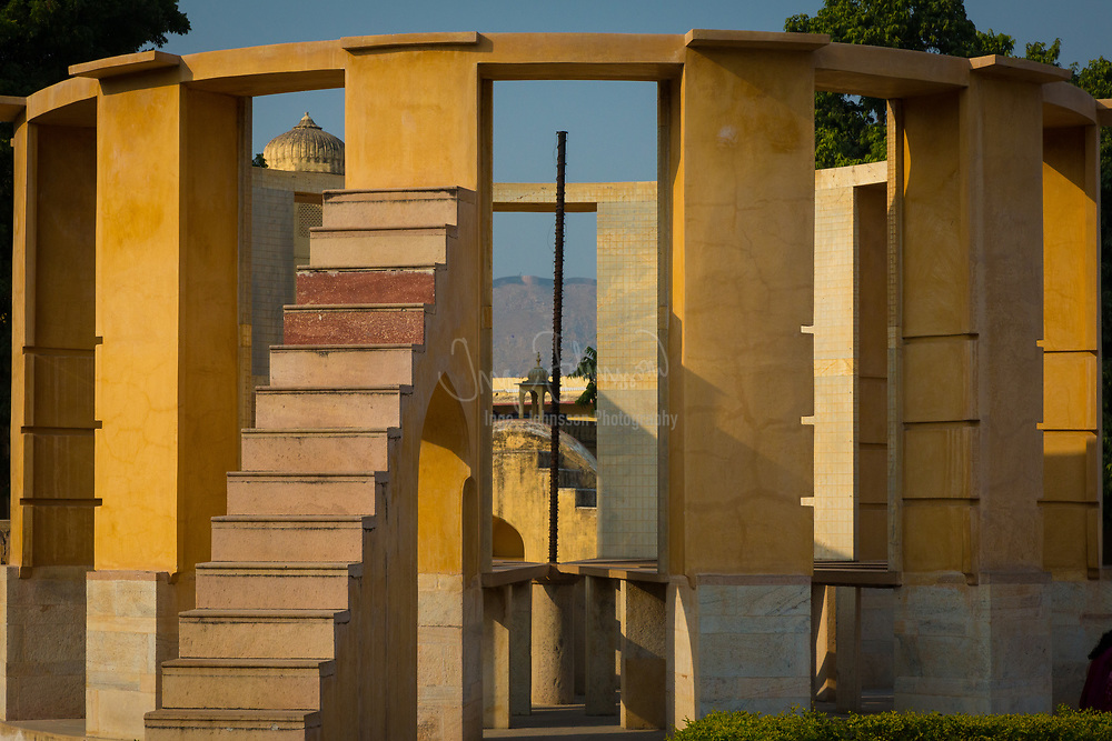 """The Jantar Mantar is a collection of architectural astronomical instruments, built by Sawai Jai Singh who was a Rajput king served Emperor Aurangzeb and later Mughals. The title of (King) and Sawai was bestowed on him by Emperor Mohammad Shah. Jai Singh II of Amber built his new capital of Jaipur between 1727 and 1734. It is also located in Ujjain and Mathura. It is modeled after the one that he had built at the Mughal capital of Delhi. He had constructed a total of five such facilities at different locations, including the ones at Delhi and Jaipur. The Jaipur observatory is the largest and best preserved of these. It has been inscribed on the World Heritage List as """"an expression of the astronomical skills and cosmological concepts of the court of a scholarly prince at the end of the Mughal period"""". Early restoration work was undertaken under the supervision of Major Arthur Garrett, a keen amateur astronomer, during his appointment as Assistant State Engineer for the Jaipur District. The jantar mantar was made by sawai jai singh as he was particularly interested in learning about the sky above his head. The observatory consists of fourteen major geometric devices for measuring time, predicting eclipses, tracking stars' location as the earth orbits around the sun, ascertaining the declinations of planets, and determining the celestial altitudes and related ephemerides. Each is a fixed and 'focused' tool. The Samrat Yantra, the largest instrument, is 90 feet (27 m) high, its shadow carefully plotted to tell the time of day. Its face is angled at 27 degrees, the latitude of Jaipur. The Hindu chhatri (small cupola) on top is used as a platform for announcing eclipses and the arrival of monsoons.<br /> Built from local stone and marble, each instrument carries an astronomical scale, generally marked on the marble inner lining. Bronze tablets, all extraordinarily accurate, were also employed. Thoroughly restored in 1901, the Jantar Mantar was declared a national monument"""