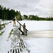 Two women chatting whilst ice swimming at Luonetjarvi lake, Tikkakoski; Central Finland. Ice swimming takes place in a body of water with a frozen crust of ice, which requires a hole cutting in it.  In Finland, the ice swimming tradition has generally been connected with the sauna tradition and it is not seen as an ascetic or religious ritual, but as a way to cool off rapidly after staying in the sauna and as a stress relief.