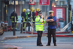 © Licensed to London News Pictures . 13/07/2013 . Manchester , UK . Police on the scene where a fireman has died . A fire fighter is dead and two 15 year old girls are under arrest on suspicion of manslaughter after a blaze in Manchester yesterday (Saturday 13th July) . More than 60 fire fighters tackled a blaze at Paul's Hair World on Oldham Street in Manchester City Centre late in to the night (Saturday 13th July 2013) . Twelve crews from four stations were deployed . Several streets in a block in the city centre are sealed off . Photo credit : Joel Goodman/LNP