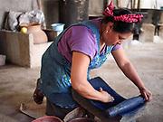 Master dyer Juana Gutierrez Contreras preparing indigo using a metate grinding stone in the Zapotec village of Teotitlan del Valle, Oaxaca, Mexico on 25 November 2018