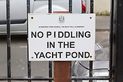 Funny sign saying No Piddling in the Yacht Pond paddling pool at Aldeburgh, Suffolk, England, UK