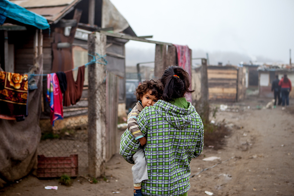 Elvira Ribarova carrying her child in the Roma settlement located in 'Budulovska Street' in Moldava nad Bodvou (2012). The city has roughly 11200 inhabitants, about 1980 (18%) of them have Roma ethnicity and around 800 are living at the segregated settlement 'Budulovska Street' (2014).