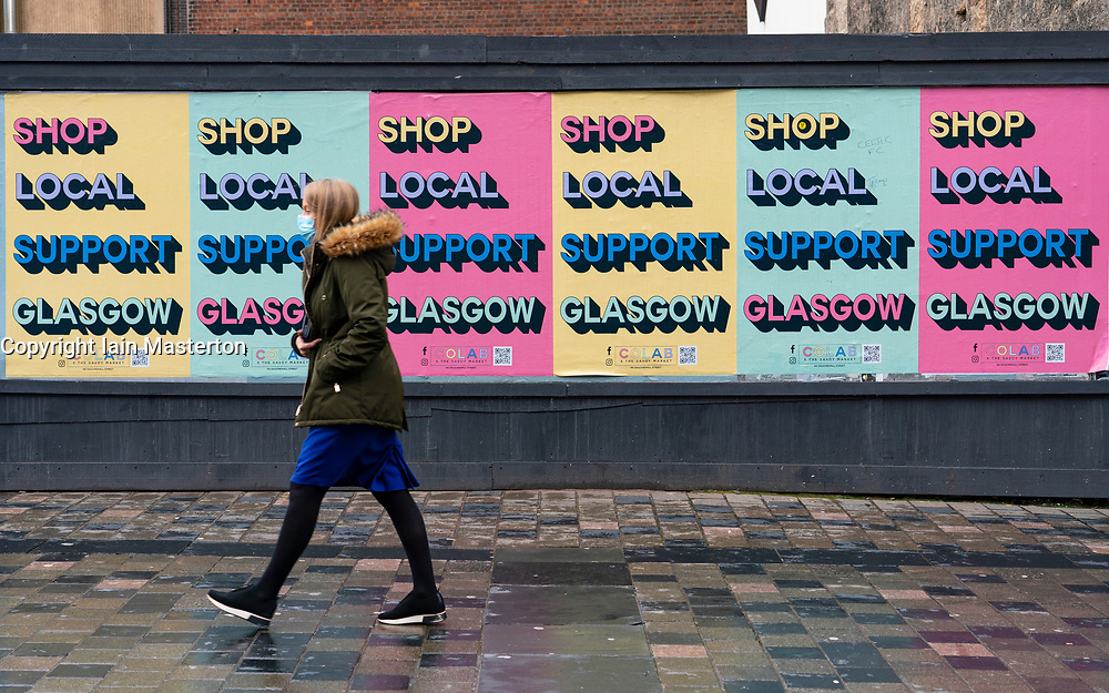 Glasgow,Scotland, UK. 2 November 2020. As Scotland enters new Coronavirus lockdown regulations the central belt and Glasgow are placed in Level 3 . Members of the public are seen out on the streets of central Glasgow for shopping and work. Pictured; Woman walks past billboard with posters showing support for Glasgow shops. Iain Masterton/Alamy Live News