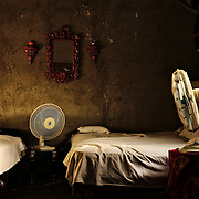 A room split between two men in Cienfuegos, the scorching  heat of July explains those fans.
