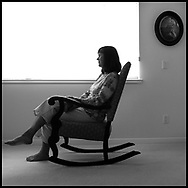 With a photo of her mother as a young girl behind her, Margo Requarth sits in a rocking chair near a window at her home in Sebastopol on July 5, 2006...Requarth, whose mother committed suicide when Margo was a child, was one of thousands of Bay Area Residents who helped raise money for the American Foundation for Suicide Prevention, AFSP, during the organization's Out of the Darkness, Walk to Prevent Suicide in San Francisco, CA on July 22, 2006...Photo by Erin Lubin