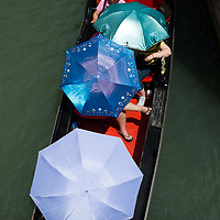A group of tourists tries to find shelters under umbrella while on a Gondola Tour on the day the Italian Government and Heath Ministry has issued several warning for the current heath wave The gondola is a traditional, flat-bottomed Venetian rowing boat, well suited to the conditions of the Venetian lagoon.