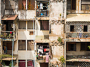 24 FEBRUARY 2015 - PHNOM PENH, CAMBODIA: Exterior of the White Building in Phnom Penh. The White Building, the first modern apartment building in Phnom Penh, originally had 468 apartments, and was opened the early 1960s. The project was overseen by Vann Molyvann, the first Cambodian architect educated in France. The building was abandoned during the Khmer Rouge occupation. After the Khmer Rouge were expelled from Phnom Penh in 1979, artists and dancers moved into the White Building. Now about 2,500 people, mostly urban and working poor, live in the building. Ownership of the building is in dispute. No single entity owns the building, some units are owned by their occupants, others units are owned by companies who lease out apartments. Many of the original apartments have been subdivided since the building opened and serve as homes to two or three families. The building has not been renovated since the early 1970s and is in disrepair. Phnom Penh officials have tried to evict the tenants and demolish the building but residents refuse to move out.   PHOTO BY JACK KURTZ