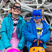 Jade and Micah Goodrich play Batgirl and Batman on Halloween at the town square in Jackson, Wyoming.