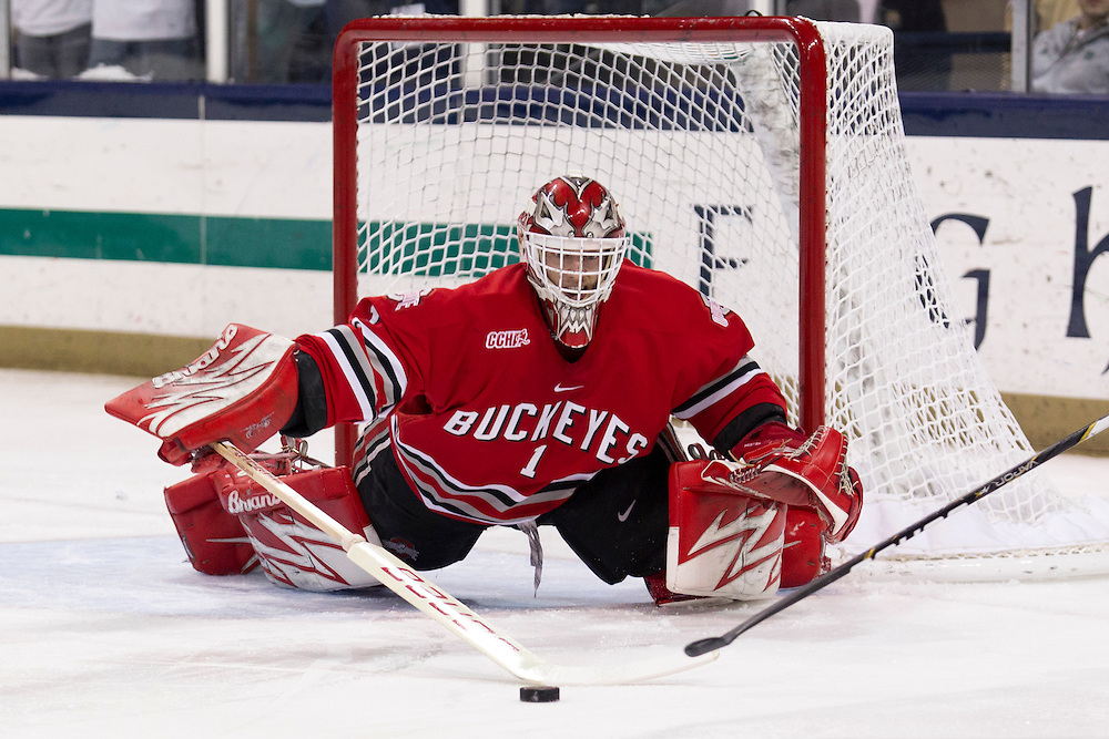 Ohio State goaltender Cal Heeter (#1) clears the puck from the crease in first period action of NCAA hockey game between Notre Dame and Ohio State.  The Notre Dame Fighting Irish defeated the Ohio State Buckeyes 4-2 in game at the Compton Family Ice Arena in South Bend, Indiana.