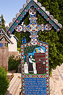 Tombstone showing a couple threshing wheat, The  Merry Cemetery ( Cimitirul Vesel ),  Săpânţa, Maramares, Northern Transylvania, Romania.  The naive folk art style of the tombstones created by woodcarver  Stan Ioan Pătraş (1909 - 1977) who created in his lifetime over 700 colourfully painted wooden tombstones with small relief portrait carvings of the deceased or with scenes depicting them at work or play or surprisingly showing the violent accident that killed them. Each tombstone has an inscription about the person, sometimes a light hearted  limerick in Romanian. .<br /> <br /> Visit our ROMANIA HISTORIC PLACXES PHOTO COLLECTIONS for more photos to download or buy as wall art prints https://funkystock.photoshelter.com/gallery-collection/Pictures-Images-of-Romania-Photos-of-Romanian-Historic-Landmark-Sites/C00001TITiQwAdS8