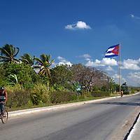 Central America, Cuba, Cienfuegos. Cuban on bike and Cuban flag on road between Cienfuegos and Trinidad.