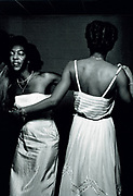 Girls wearing long dresses, dancing together. Photo by Richard Saunders 1983